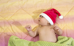 Portrait of a newborn baby boy with santa's hat in bed Royalty Free Stock Photos
