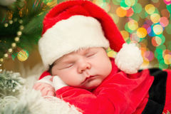 Portrait of newborn baby in Santa clothes lying under Christmas tree. Royalty Free Stock Images