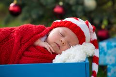Portrait of newborn baby in Santa clothes lying under Christmas Stock Images