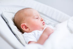 Portrait of newborn baby sleeping in bouncer chair Stock Photo
