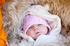 Portrait of newborn baby in warm winter clothes. Beautiful cute girl in warm overall, cap. Peaceful child sleep during. Outdoor walk stock photo