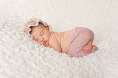 Portrait of a Newborn Girl with Lace Pants and Bonnet. Full length shot of a sleeping two week old newborn baby girl wearing a lacy bonnet and lavender colored Stock Photo