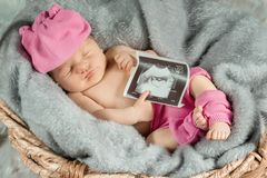 Portrait of a newborn girl. With a photo of an ultrasound in the hand Royalty Free Stock Photos