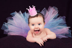 Portrait of newborn girl smiling in a pink crown Stock Photos