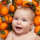 Portrait of newborn happy baby with mandarin Stock Photo