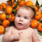 Portrait of newborn happy baby with mandarin Stock Image