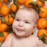 Portrait of newborn happy baby with mandarin Stock Photo