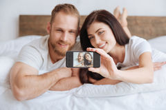 Portrait of newly married couple taking selfie in bed Stock Image