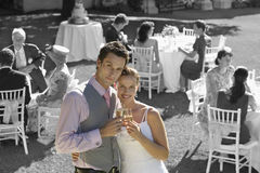 Portrait of newly wedded couple with champagne glasses at wedding reception Stock Photos
