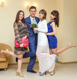 Portrait of newlywed couple having fun with bridesmaids. Indoors Stock Photography