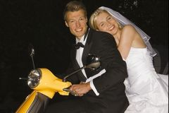 Portrait of a newlywed couple on a motor scooter and smiling Stock Image