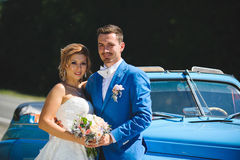 Portrait of Newlyweds. By blue car Royalty Free Stock Photography