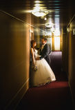 Portrait of newlyweds hugging in long hotel hallway Stock Photography