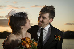 Portrait of newlyweds looking at eachother. Lovingly Stock Photography