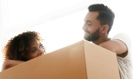 Portrait of the newlyweds near the box with things for moving. Close-up of the newlyweds near the box with things for moving. Concept of family happiness Royalty Free Stock Images