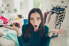 Portrait of nice attractive charming funny tired cheerful cheery girl among different clothes making choice what to put. On in light white interior dressing royalty free stock photos