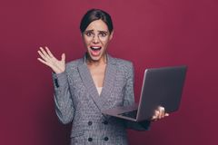 Portrait of nice attractive classy crazy nervous lady financier director ceo boss chief in gray checkered blazer holding. In hands laptop resent  over maroon stock images