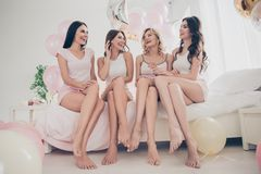 Portrait of nice attractive lovely fit thin slim well-groomed cheerful girlfriends having fun sitting on bed barefoot royalty free stock photos