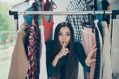 Portrait of nice attractive pretty charming cheerful cheery funny brunette girl lady hiding among clothes conspiracy in. Dressing room royalty free stock photo