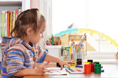 Baby draws paints at the table Stock Photography