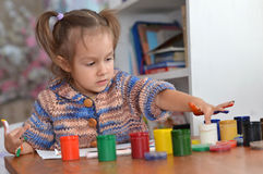 Girl draws paints at the table Stock Photos