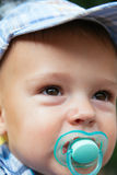 Portrait of a nice baby with pacifier Stock Images