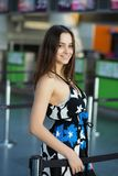 Portrait of nice brunette. Posing standing at the airport wearing a dress royalty free stock photo