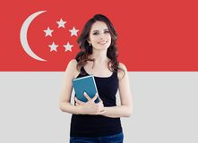 Portrait of nice brunette woman student with the Singapore flag background royalty free stock photos