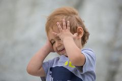 Little boy covers his face with his hands Stock Photography