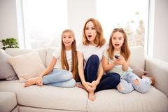 Portrait of nice cute amazed stunned lovely attractive charming cheerful cheery positive ginger hair people mom mommy. Mum pre-teen girls sitting on divan stock images