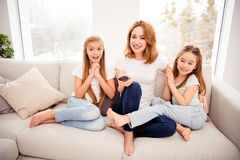 Portrait of nice cute lovely attractive adorable cheerful cheery positive people mom mommy mum pre-teen girls sitting on. Divan watching funny cartoon in house royalty free stock photo