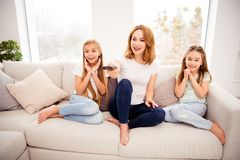 Portrait of nice cute lovely attractive charming cheerful cheery positive sweet blonde people mom mommy mum pre-teen. Girls sitting on divan watching funny royalty free stock images