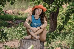 Portrait of nice girl in cowboy hat. Enviable young woman sits on a stump the backdrop of the garden Stock Photo