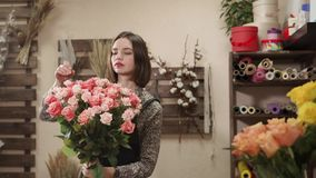 Charming female florist with a bouquet. Portrait of a nice girl with a dozens of pink roses indoor. She is assembling a beautiful bouquet stock video