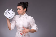 Portrait of nice girl holding big clock in her Royalty Free Stock Images