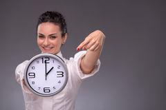 Portrait of nice girl holding big clock in her Royalty Free Stock Photo