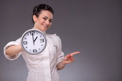 Portrait of nice girl holding big clock in her Stock Photo