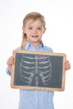 Portrait of nice girl with smooth hair. Little kid draws chest and heart with chalk on blackboard Royalty Free Stock Photography