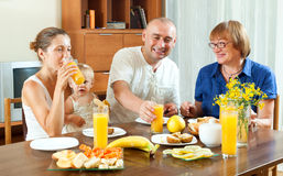 Portrait of nice happy multigeneration family  eating friuts wit Royalty Free Stock Photography