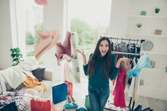 Portrait of nice-looking cute lovely attractive pretty charming puzzled uncertain girl lady throwing things away. Preparing for event in light white interior stock image
