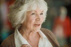 Dreamy senior woman. Portrait of nice smilig thoughtful senior woman close up royalty free stock photo
