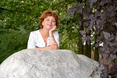 Portrait of the nice woman of average years in the park Stock Photo