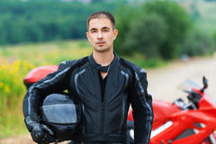Portrait nice young man helmet. Portrait nice young dreary man motorcycle holding hand helmet beside motorcycle background summer green forest Stock Photos