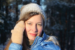 Portrait of the nice young woman in the blue jacket and a cap. Covered with snow in winter day Royalty Free Stock Photography