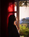 Portrait of nice young woman looks out window Royalty Free Stock Photo