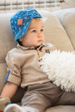 Portrait of nicely dressed little boy with blue eyes sitting on the sofa. Portrait of nicely dressed little boy with blue eyes sitting on the sofa and looking Royalty Free Stock Images