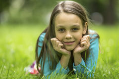 portrait of a nine year old girl lying in the green grass. Royalty Free Stock Image