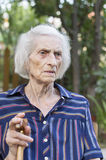 Portrait of a ninety years old woman with a walking stick outdoo Stock Photo