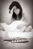 Pilules et hors de femme malade ou déprimée de foyer Image stock