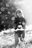 Portrait noir et blanc d'une fille s'asseyant sur un blo de banc en bois Photographie stock libre de droits